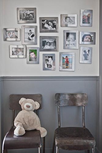 Familienbilder mit silbernen Rahmen an der Wand über zwei Stühlen