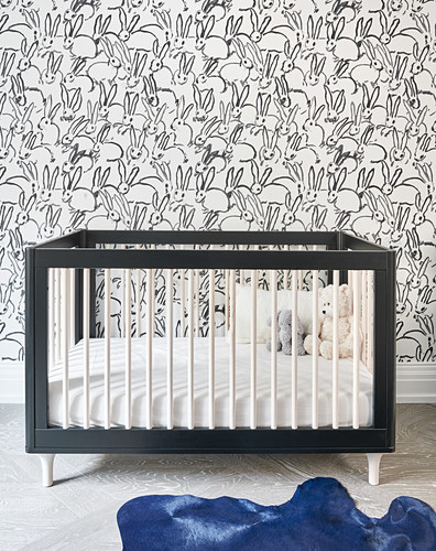 Crib, rabbit wallpaper and blue cowhide rug in nursery