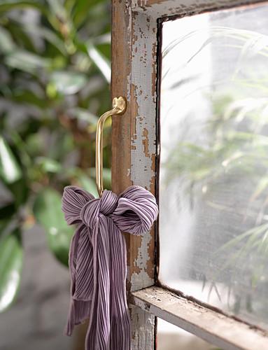 Purple cloth bow on handle of old lattice door