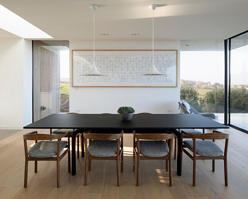 Dark table and armchairs in minimalist dining area