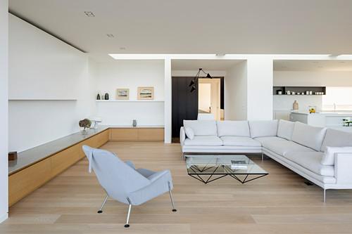 Helle Sofagarnitur, Couchtisch, Polstersessel und maßgefertigtes Lowboard in offenem Wohnraum
