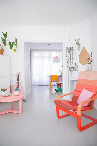 Coffee table and armchair in shades of red and pink in white, light-flooded interior