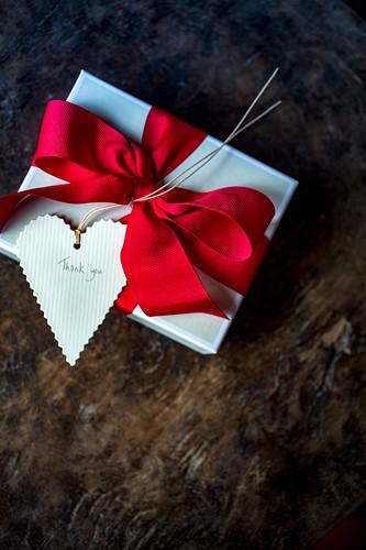 Geschenkpäckchen mit roter Schleife und Herzanhänger mit 'Thank you'