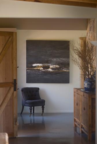 Easy chair below painting and rustic sideboard in foyer