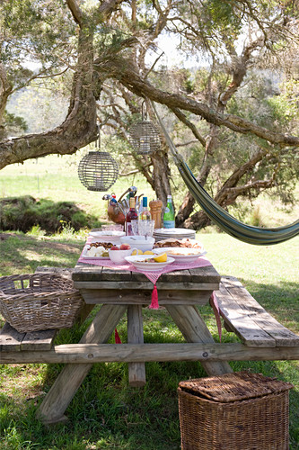 Rustic wooden picnic table set for meal in garden