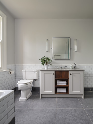 Washstand next to toilet in bathroom in shades of pale grey