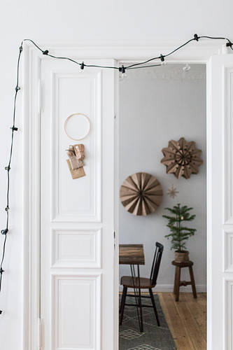 DIY Advent calendar and fairy lights hung on white door with view into festively decorated dining room