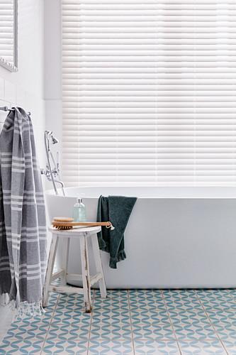 Free-standing bathtub below window with louvre blind in bathroom