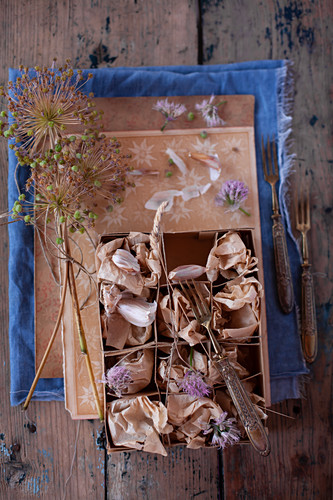 Garlic cloves and flowers wrapped in tissue paper in cardboard box