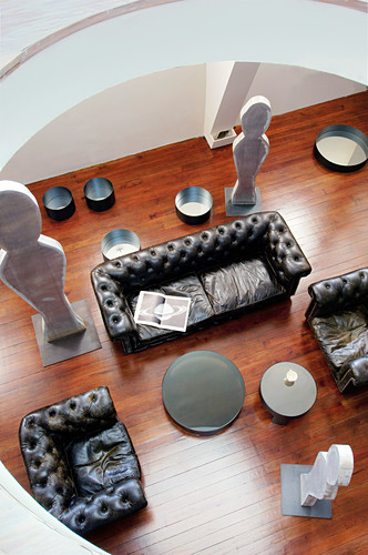 View down onto leather sofa set and sculptures in loft apartment