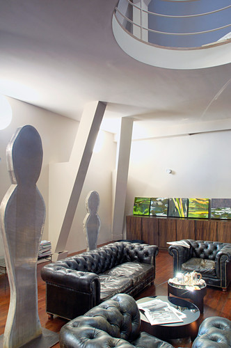 Leather sofa set and sculptures in loft apartment
