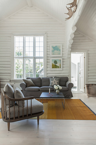 Sessel mit grauem Polster, passendes Sofa und Couchtisch in weiß gestrichenem Blockhaus