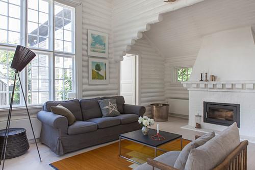 Graues Polstersofa, Klassiker-Stehleuchte und Couchtisch vor Kamin in weiß gestrichenem Blockhaus