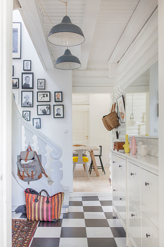 Chequered floor, gallery of photos and stairs with white banisters in hallway