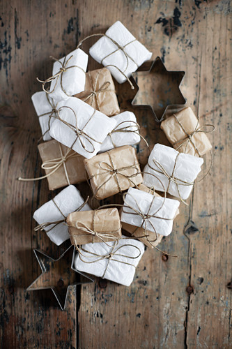 Small gifts wrapped in white and pale brown and star-shaped pastry cutters