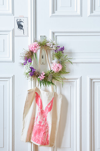 Wreath of flowers and seed heads on door with cloth bag hung below