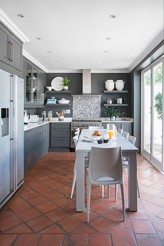 Log white table in kitchen-dining room with terracotta floor tiles