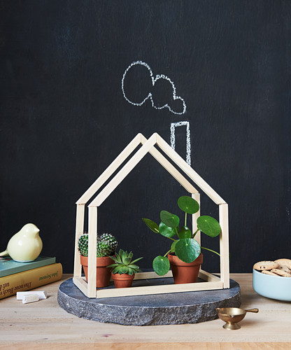 Plants in small, handcrafted wooden hut in front of chalkboard