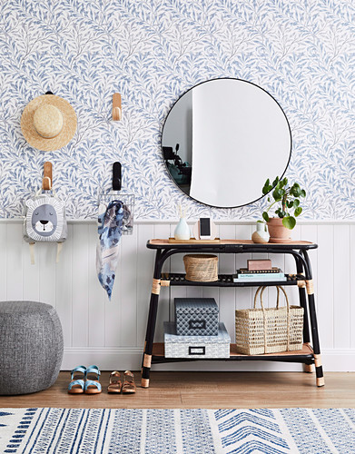 Storage idea in the hallway: table, round mirror above and wall hooks on blue and white wallpaper