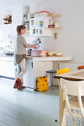 Woman standing at white kitchen counter below wall units and shelves