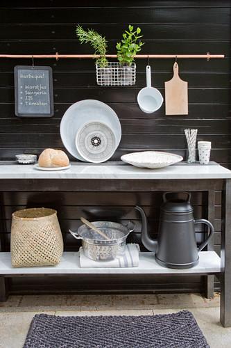 Konsolentisch mit Küchenutensilien und Giesskanen vor dunkler Holzwand auf der Terrasse
