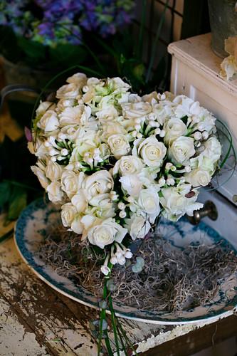 Heart-shaped arrangement of white roses and bouvardia