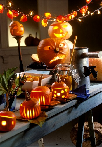 Table laid for Halloween with illuminated pumpkins