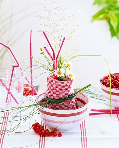 Napkin decoration of bent grass, marguerites & redcurrants