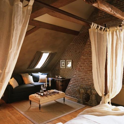 Gemütlicher Wohn-Schlafraum im traditionellen Stil mit Ziegelwand und offener Dachkonstruktion