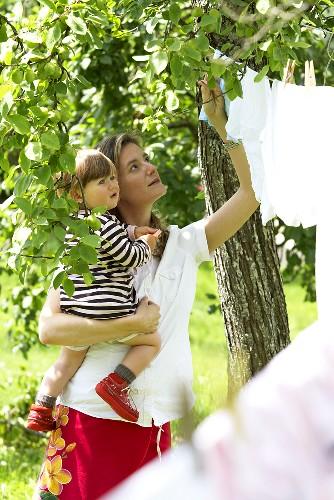 Frau mit Kind hängt Wäsche im Garten auf - Bild kaufen