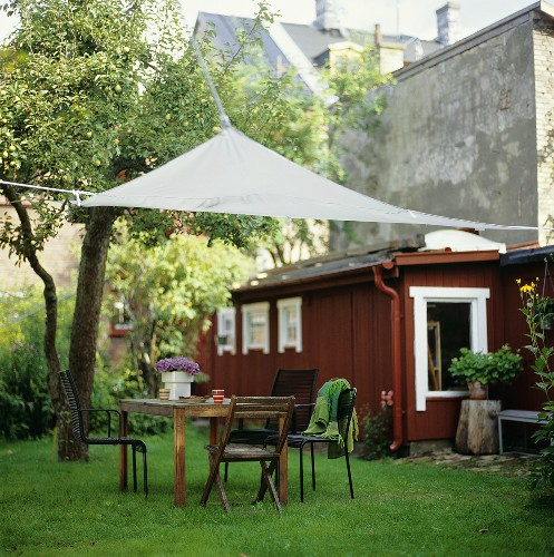 Garden table with chairs and awning out of doors