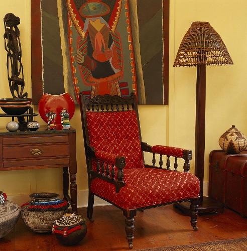Roter Sessel zwischen afrikanische Skulpturen und Mitbringsel