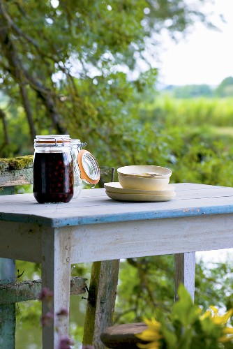 Jar of compote and tableware on a garden table