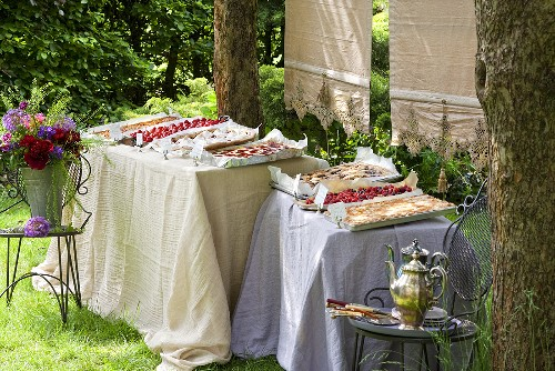 A cake buffet with tray bakes in a garden