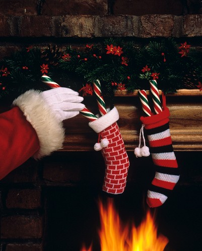 Santa Adding Candy Canes to Hanging Stockings