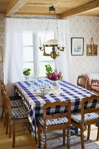 A cosy country dining room with a dining table with a checked table cloth in front of a window