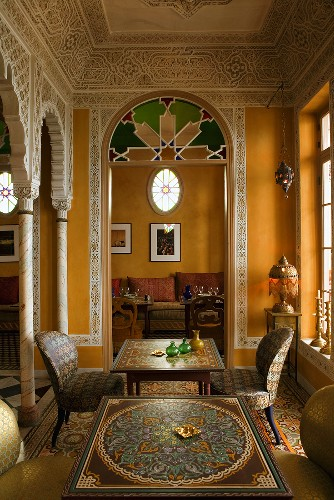 Elegant Moroccan salon with wall frescos and a view through an archway of a sofa