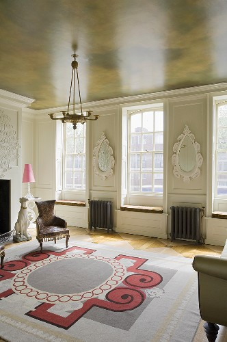 A minimalistic living room in an period building with a painted ceiling and an art deco rug on a parquet floor