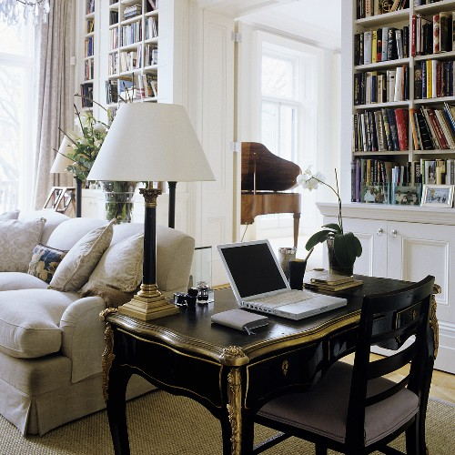 Work on a black, antique davenport with a table lamp with a white shade in front of an upholstered sofa in a library