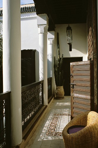 A balcony of a Moroccan house with a wicker chair and cactus