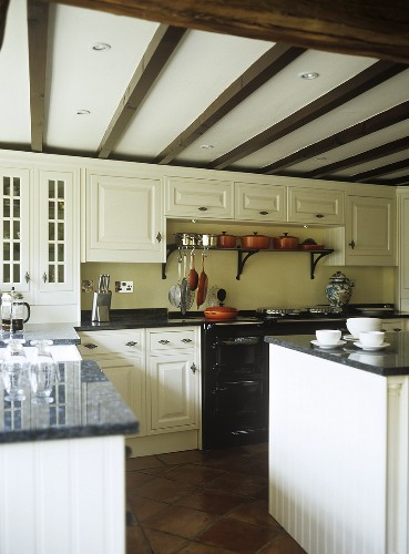 Fitted kitchen and island unit with granite worktops, utensils and crockery.