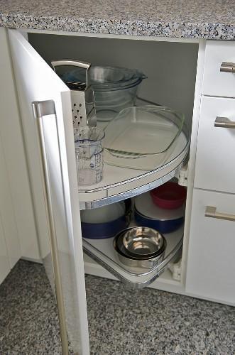 Kitchenware on storage shelves in modern kitchen unit