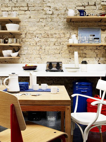 A small dining area in a kitchen in front of a white-painted stone wall