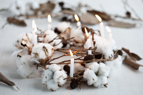 A wintry wreath made of cotton, cones and a candle