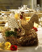 Easter table decoration: wooden cock and hen on straw nest