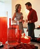 Partytisch mit Kerzen, dahinter Menschen mit Sektcocktail