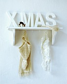 Wall shelf with the word Xmas, scarves, cap and glove