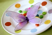 Coloured plate with chocolate beans and tulle butterfly