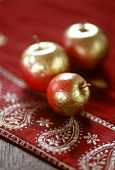 Three gilded apples as table decoration
