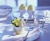 Tischgedeck mit Blumen gefüllter Eierschale